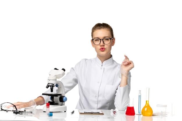 Vue de face femme médecin en costume médical blanc assis en face de la table avec des solutions sur l'espace blanc clair