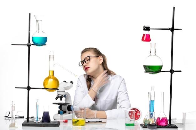 Vue de face femme médecin en costume médical blanc assis en face de la table avec des solutions sur fond blanc virus de la chimie pandémique covid