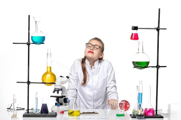 Vue de face femme médecin en costume médical blanc assis en face de la table avec des solutions sur la pandémie de chimie covid virus fond blanc