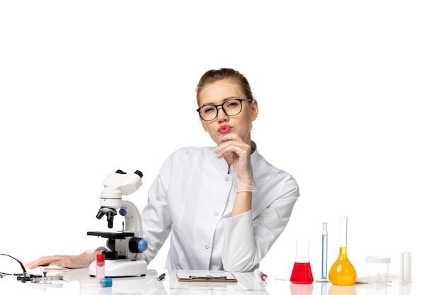 Vue de face femme médecin en costume médical blanc assis en face de la table avec des solutions de réflexion sur un espace blanc