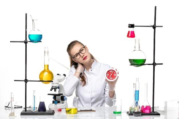 Vue de face femme médecin en costume médical blanc assis et tenant des horloges sur fond blanc virus de la chimie pandémique covid
