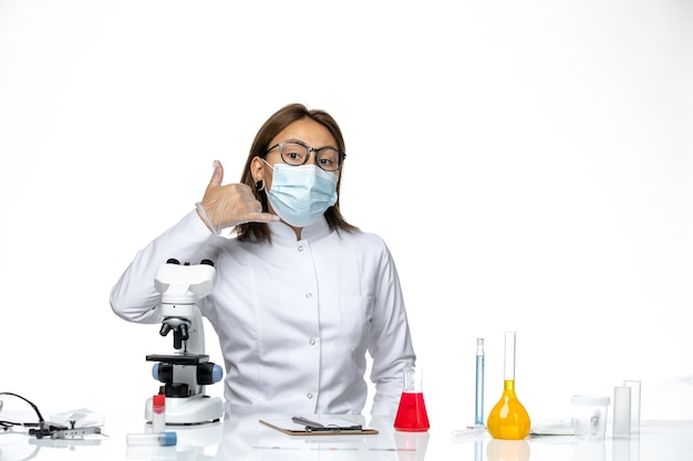 Vue de face femme médecin en costume médical blanc avec masque et gants en raison de covid posant sur l'espace blanc