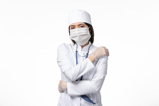 Vue de face femme médecin en costume médical blanc avec un masque en raison d'un coronavirus sur le mur blanc maladie pandémique covid-