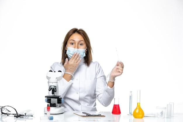 Vue de face femme médecin en costume médical blanc et masque en raison de covid à l'aide d'un microscope sur un espace blanc