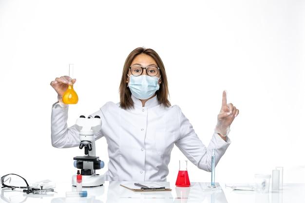 Vue de face femme médecin en costume médical blanc et masque en raison du coronavirus travaillant avec des solutions sur l'isolement pandémique du virus du plancher blanc covid
