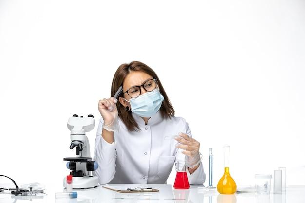 Vue de face femme médecin en costume médical blanc avec masque en raison de la pensée covid sur l'espace blanc