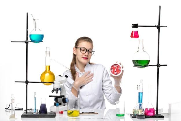 Vue de face femme médecin en costume médical blanc tenant des horloges assis sur fond blanc virus de la chimie pandémique covid