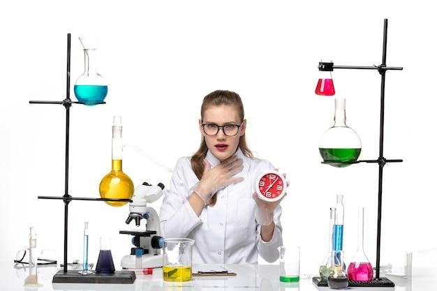 Vue de face femme médecin en costume médical blanc tenant des horloges sur le sol blanc virus de la chimie pandémique covid