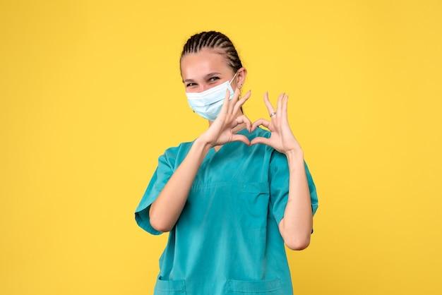 Vue de face de la femme médecin en costume médical et masque stérile sur mur jaune