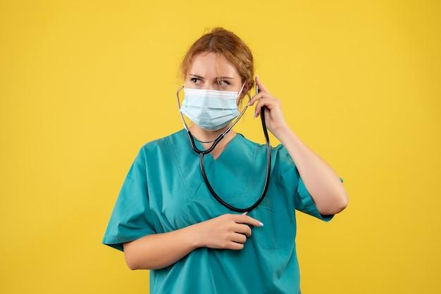 Vue de face de la femme médecin en costume médical et masque avec stéthoscope sur mur jaune