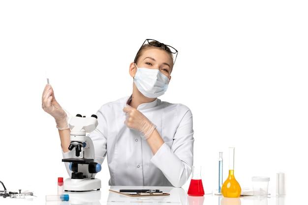 Vue de face femme médecin en costume médical portant un masque en raison de covid travaillant avec des solutions sur un bureau blanc