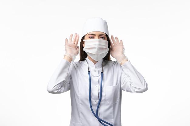 Vue de face femme médecin en costume médical stérile blanc avec masque en raison d'un coronavirus essayant d'entendre sur le mur blanc maladie covid- maladie à virus pandémique