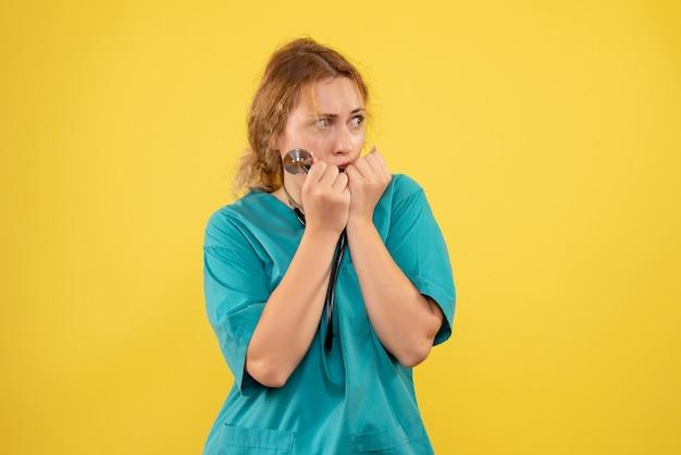 Vue de face de la femme médecin en costume médical avec stéthoscope sur mur jaune