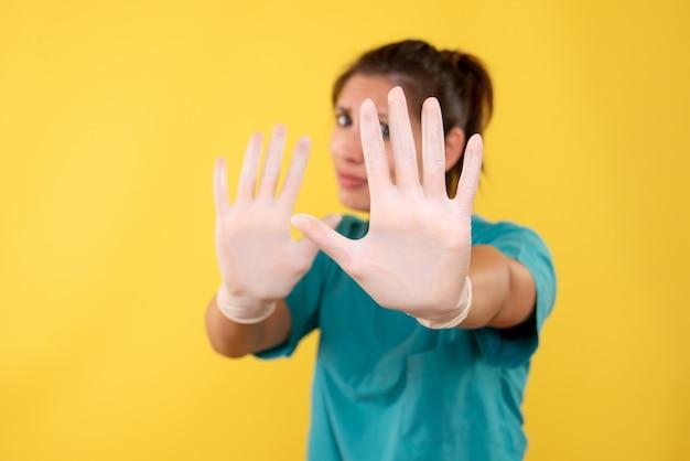 Vue de face femme médecin dans des gants médicaux sur fond jaune