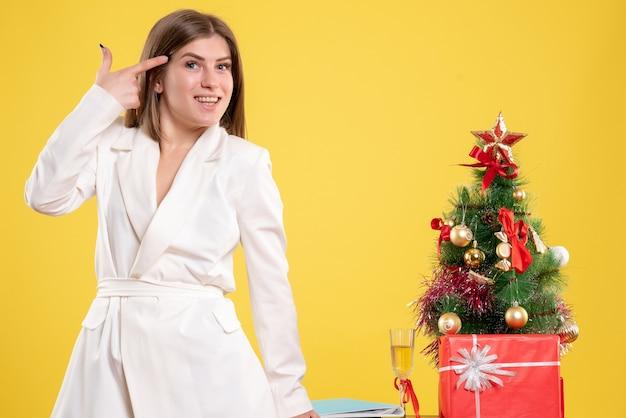 Vue de face femme médecin debout autour de la table avec des cadeaux de noël et arbre sur fond jaune avec arbre de noël et coffrets cadeaux