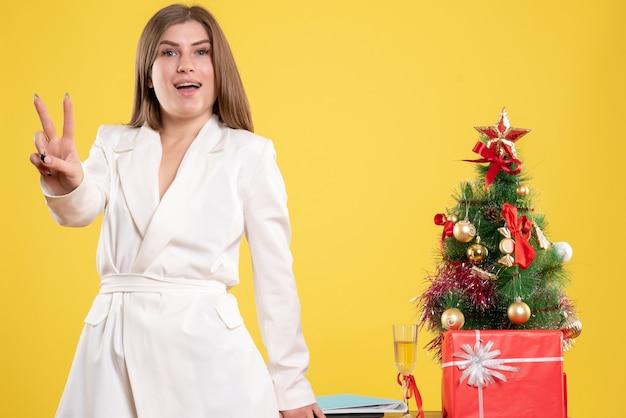 Vue de face femme médecin debout autour de la table avec petit arbre de noël sur fond jaune avec arbre de noël et coffrets cadeaux