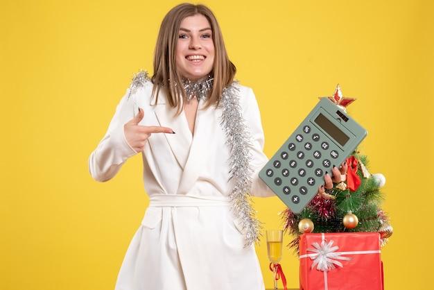 Vue de face femme médecin debout et tenant la calculatrice sur un bureau jaune avec arbre de noël et coffrets cadeaux