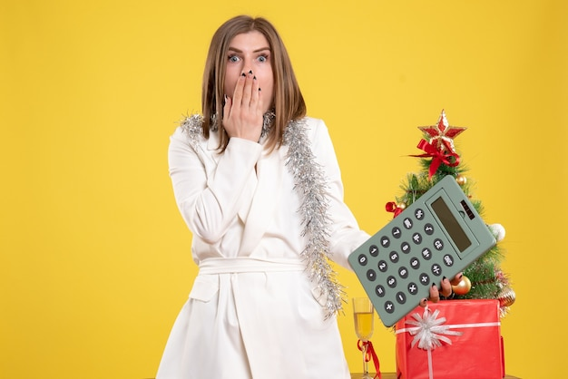 Vue de face femme médecin debout et tenant la calculatrice sur fond jaune avec arbre de noël et coffrets cadeaux