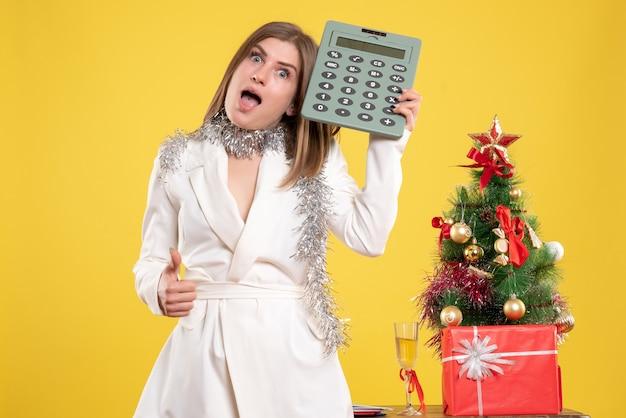 Vue de face femme médecin debout et tenant la calculatrice sur jaune avec arbre de noël et coffrets cadeaux