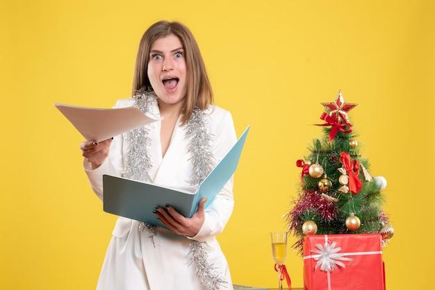 Vue de face femme médecin debout et tenant des documents sur un bureau jaune avec arbre de noël et coffrets cadeaux
