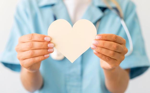 Vue de face de la femme médecin défocalisé tenant coeur de papier
