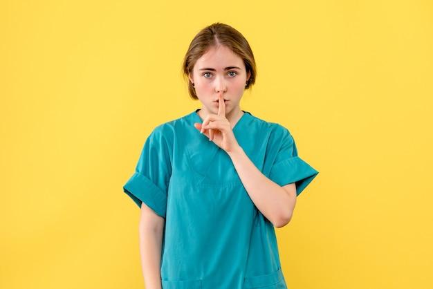 Vue de face femme médecin demandant de se taire sur fond jaune émotion hôpital santé medic