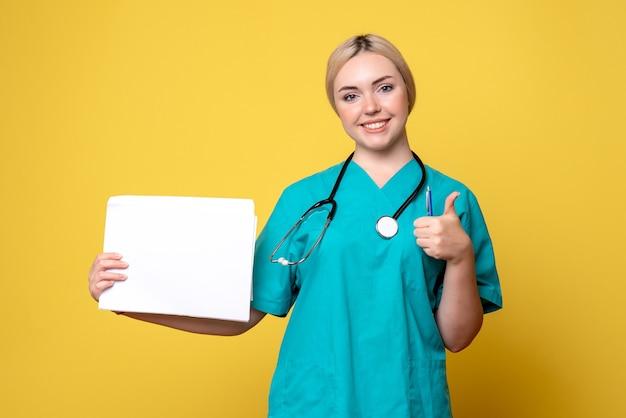 Vue de face femme médecin détenant différents papiers, infirmière de l'hôpital de la pandémie de virus de la santé médicale covid-19