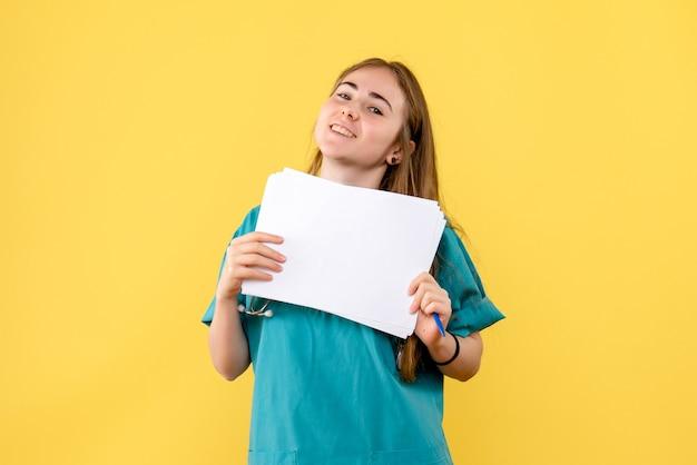 Vue de face femme médecin avec documentation sur un hôpital de santé infirmière fond jaune