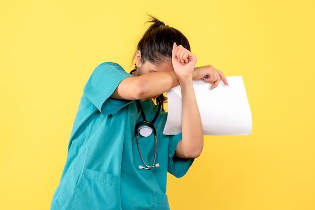 Vue de face femme médecin avec des documents couvrant sa tête