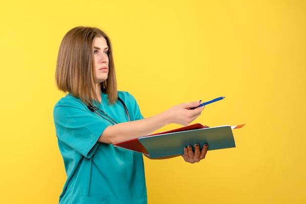 Vue de face femme médecin avec des documents sur l'espace jaune