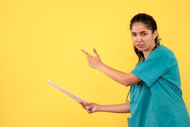 Vue de face femme médecin avec des documents pointant vers l'arrière