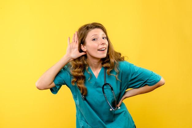 Vue de face de la femme médecin à l'écoute sur le mur jaune