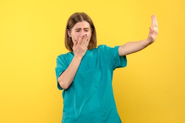 Vue de face de femme médecin avec expression nerveuse sur mur jaune