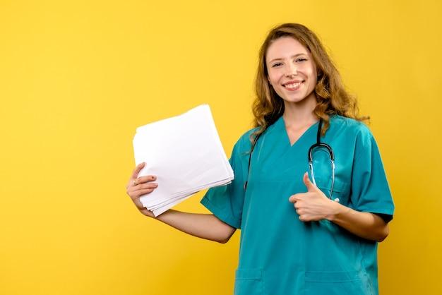 Vue de face femme médecin avec des fichiers sur l'espace jaune