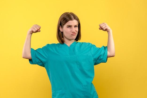 Vue de face femme médecin fléchissant sur l'espace jaune