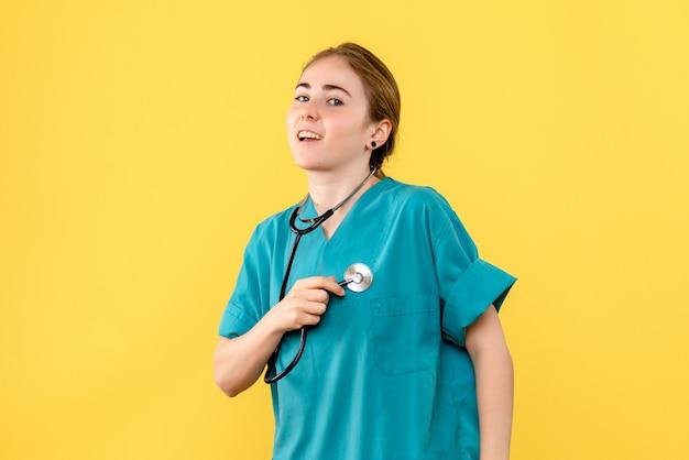 Vue de face femme médecin sur fond jaune médical émotion santé de l'hôpital