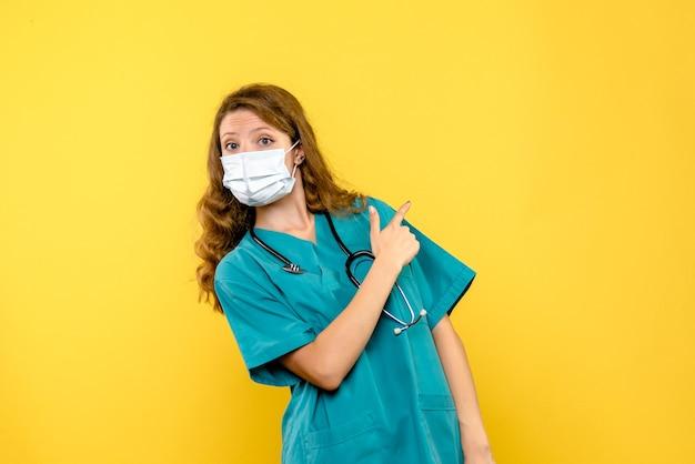 Vue de face femme médecin en masque sur espace jaune clair