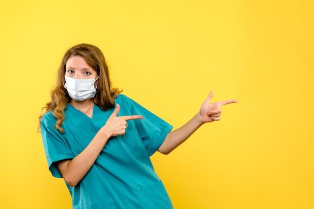Vue de face femme médecin en masque sur espace jaune