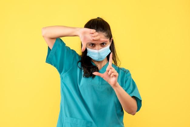 Vue de face femme médecin avec masque faisant signe de la caméra