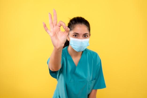 Vue de face de la femme médecin avec masque faisant signe okey devant l'avant sur le mur jaune
