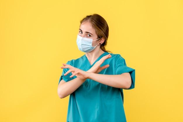 Vue de face femme médecin en masque sur fond jaune pandémie de l'hôpital de covid-santé