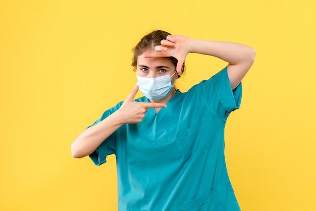 Vue de face femme médecin en masque sur fond jaune pandémie de l'hôpital de santé covid