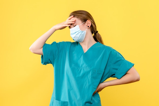 Vue de face femme médecin en masque sur fond jaune virus pandémie de santé covid-