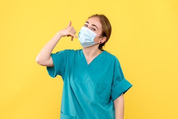 Vue de face femme médecin en masque sur fond jaune virus de la santé pandémique covid
