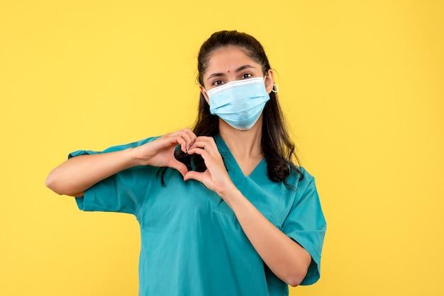 Vue de face femme médecin avec masque médical signe de coeur makng avec les doigts