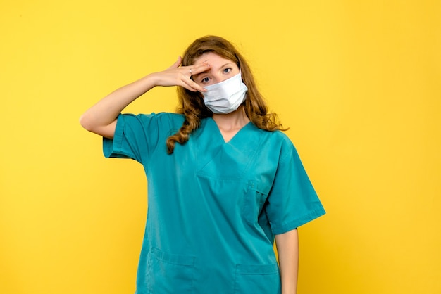 Vue de face de la femme médecin en masque sur mur jaune