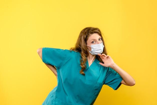 Vue De Face De La Femme Médecin En Masque Sur Mur Jaune Photo gratuit