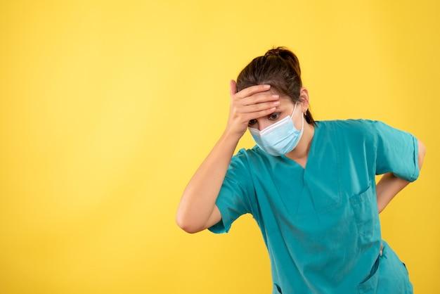 Vue de face femme médecin en masque de protection sur fond jaune