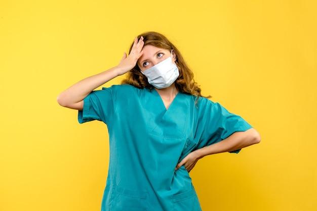 Vue de face de la femme médecin en masque de réflexion sur mur jaune