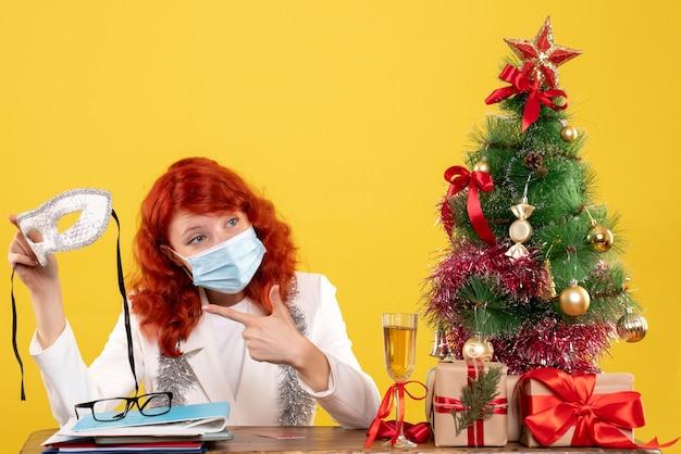 Vue de face femme médecin en masque stérile tenant un masque de fête autour de cadeaux de noël